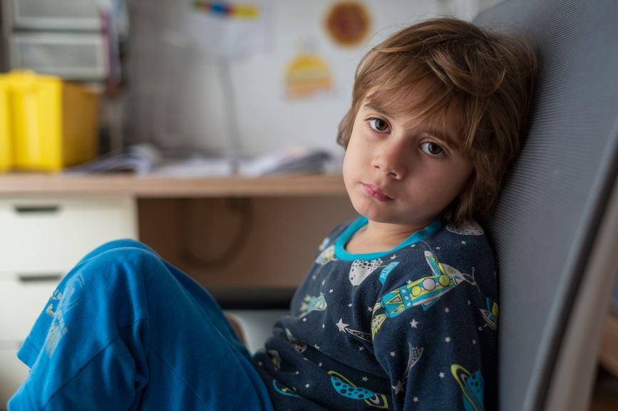 young boy in his bedroom and space pajamas on, staring at camera with attitude