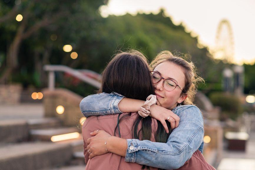 two teenage girls hugging outside