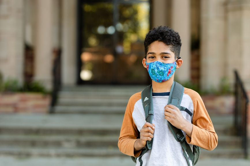 boy wearing mask outside school with backpack on