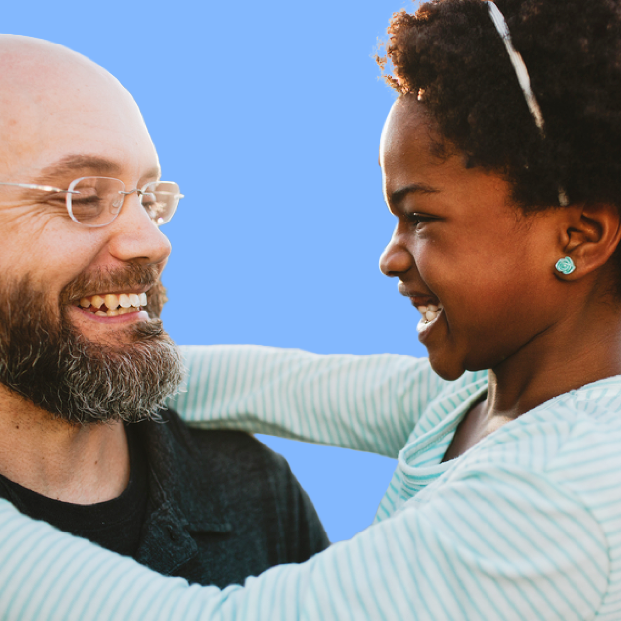 Dad smiling with school-age daughter