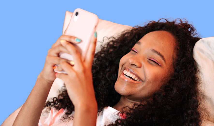 Girl using iPhone and laughing