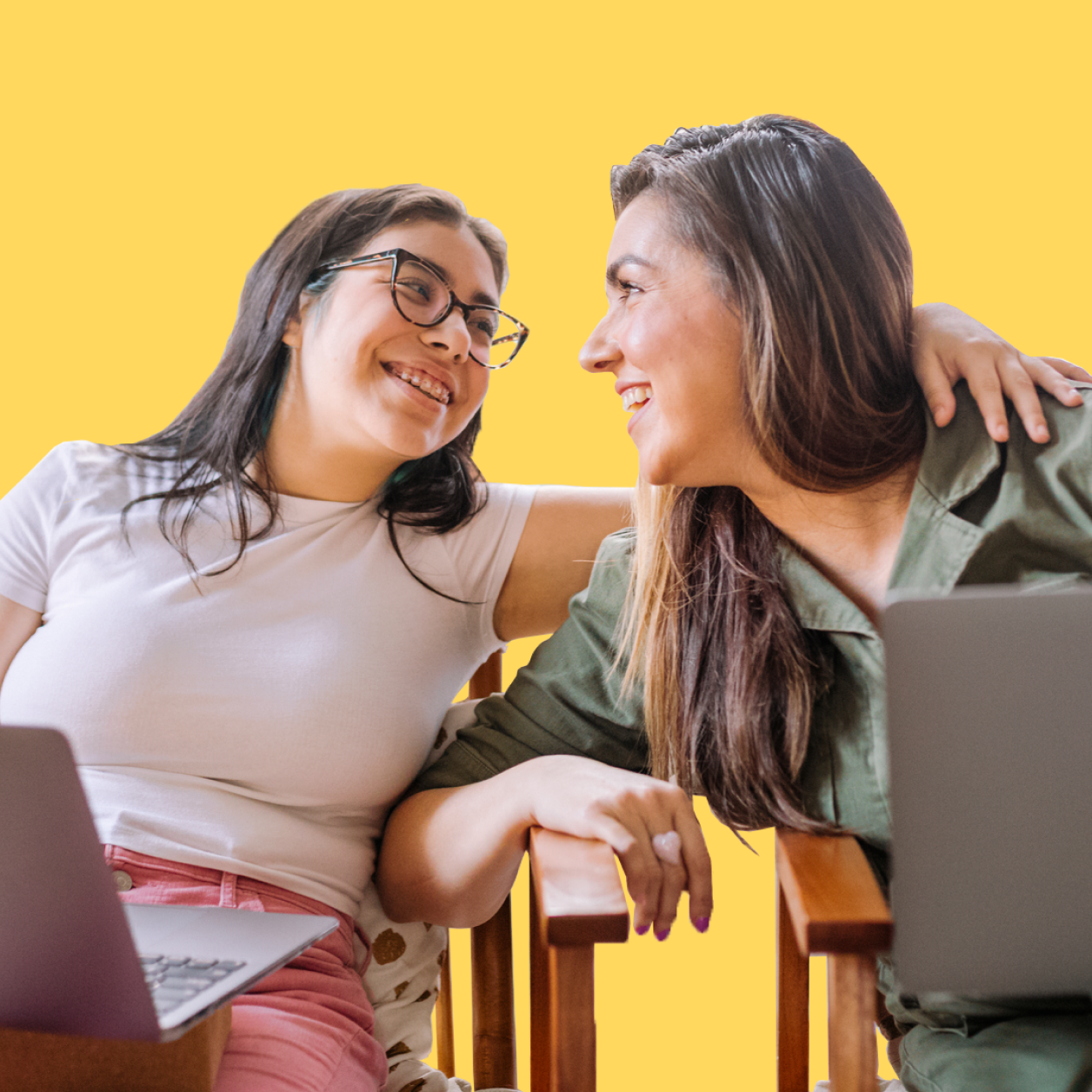 Teenage girl and mom with laptops laughing together, girl's arm around her mother