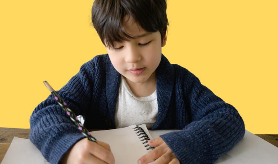 Boy writing on notebook